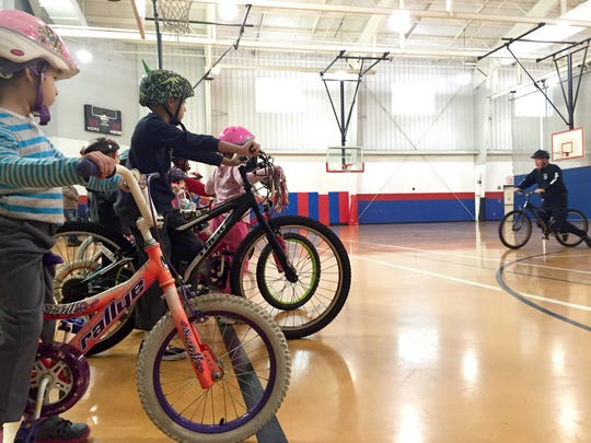 """Master Corporal Brian Whitte, center, leads lessons at the Wilmington Police Athletic League's """"How to Ride a Bike"""" program."""