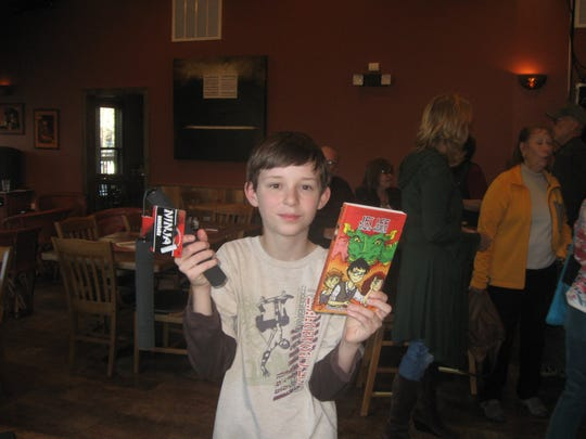 Topher shows off his copy of Pamela K. Witte's book that he picked up at her book release party at Sacred Grounds Coffee and Tea House.