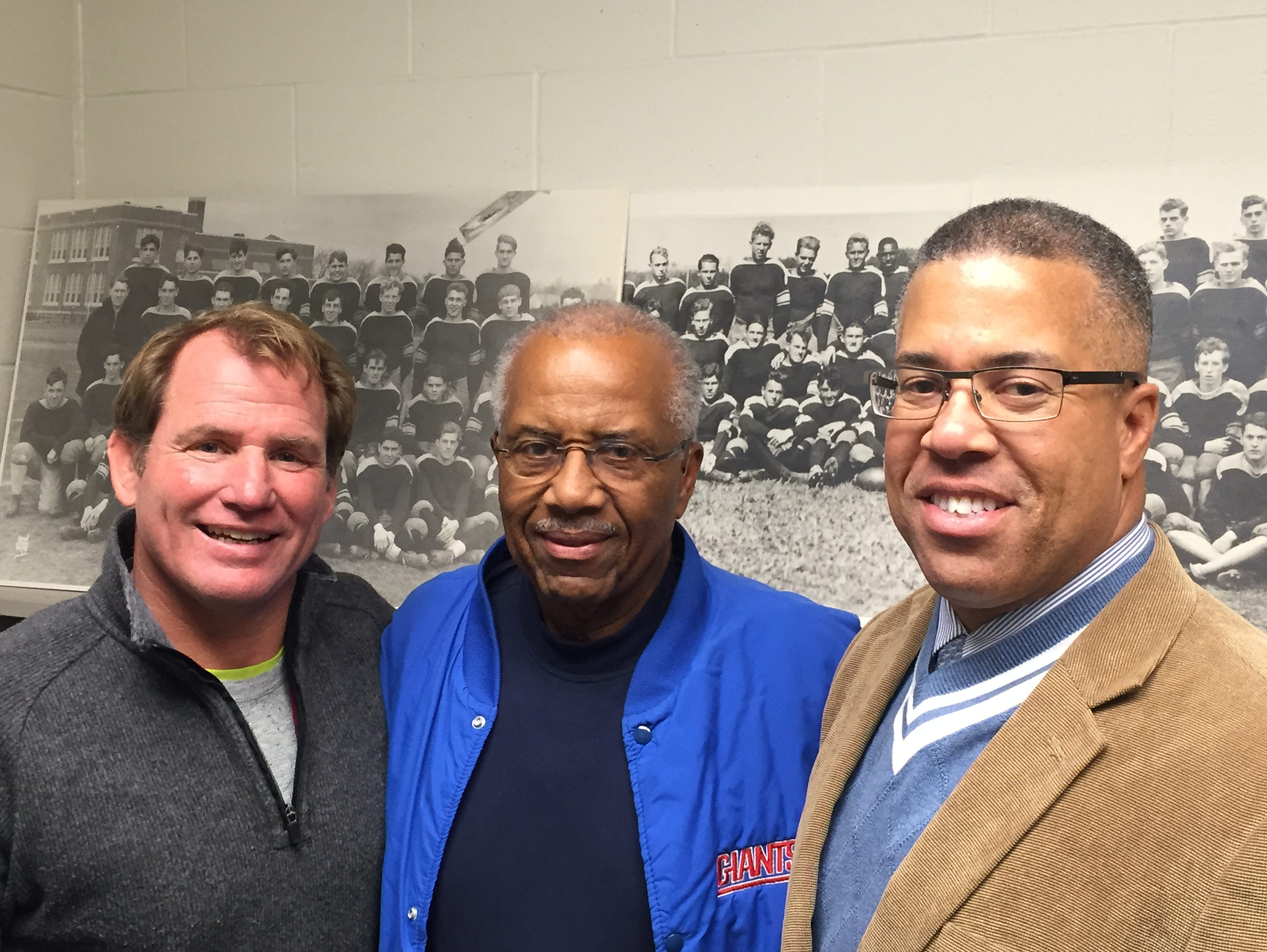 Standing in front of photos of Long Branch football teams from the 1930s, (from left to right) current head coach Dan George, Wesley Mayo Sr. and Wesley Mayo Jr. all played for the Green Wave over the years, and all played against Red Bank on Thanksgiving Day.