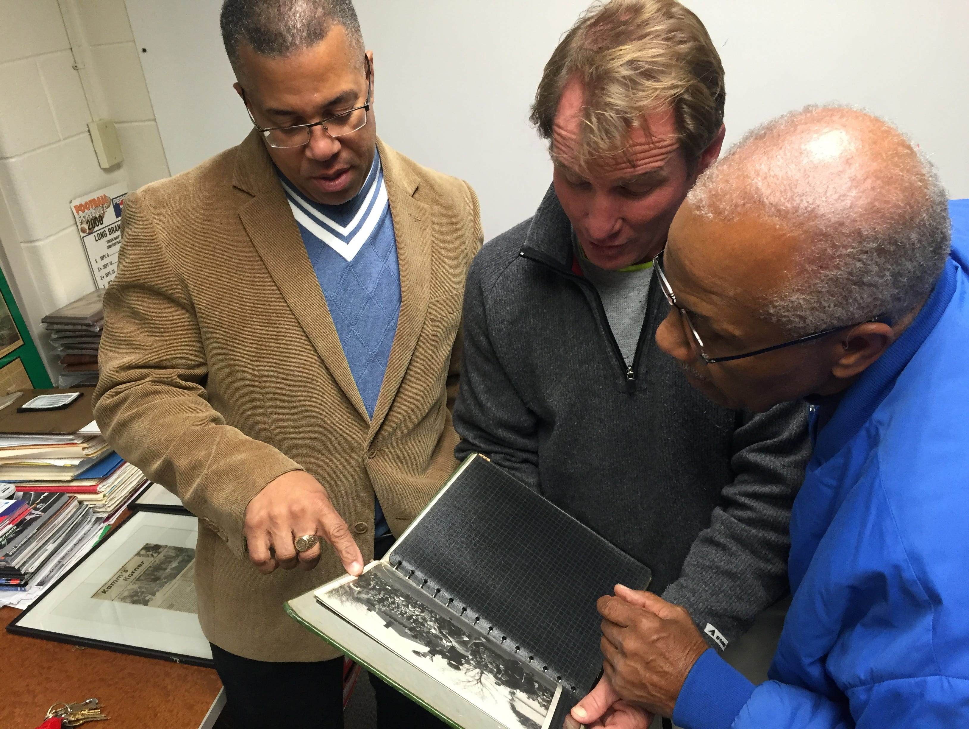 Looking at a scrapbook of the 1957 Long Branch football season are (left to right) Wesley Mayo Jr., current Long Branch head coach Dan George, and Wesley Mayo Sr., who played on the 1957 team with George's father, William George Jr.