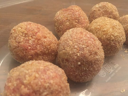 Wee scotch eggs feature seasoned sausage wrapped around quail eggs and breaded with breadcrumbs.