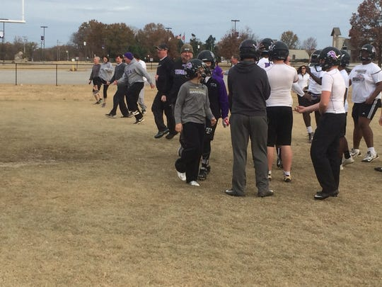 A few TCA dads go through warm-up drills before the team's practice Thursday morning.