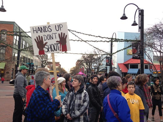 """About 25 people marched down Church Street on Friday chanting """"we won't stop, we won't shop, we won't stop til black lives matter."""""""