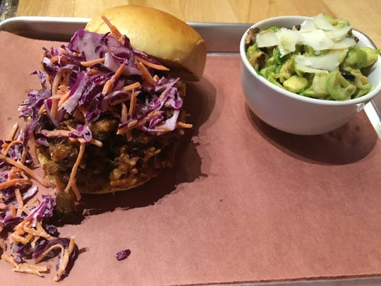 Guru BBQ's barbecue pork sandwich with sweet and tangy slaw on a brioche bun and a chopped salad.