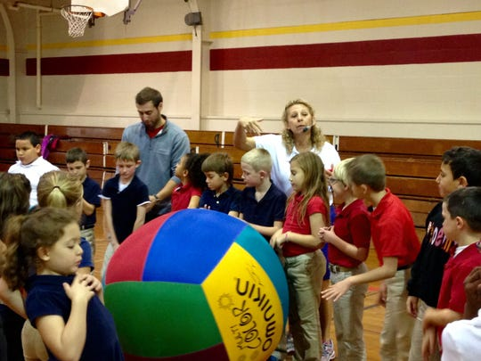 Phoenix Magnet Elementary physical education teacher Teresa Guillot (back, in white)  reminds second-graders of the rules of Omnikin, a Canadian game, during class Monday. Guillot was named Recreator of the Year for the state.