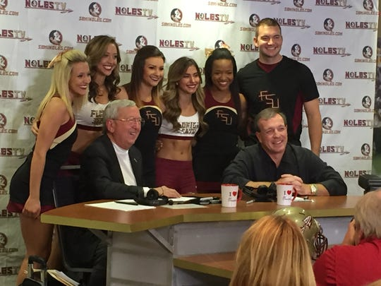Florida State coach Jimbo Fisher, right, and radio host Gene Deckerhoff, left, post for a photo with several FSU cheerleaders  during his final radio call-in show of the season on Wednesday, Dec. 2, 2015.