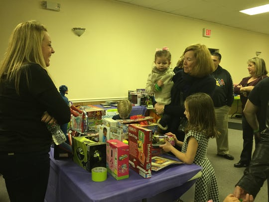 "Jen Oconnor of Spotswood, Kathy Doherty of Spotswood, Gabby Doherty of Westfield and Lila Hricko of Fairfield look over some of the toys collected at the ""Gift Card, DVD Movie and Toy Drive"" hosted by the Szatkoswki family in memory of their son, Jeffrey Szatkowski Jr., who, along with his girlfriend Nicole Surace, died in a car accident on Dec. 1, 2013."