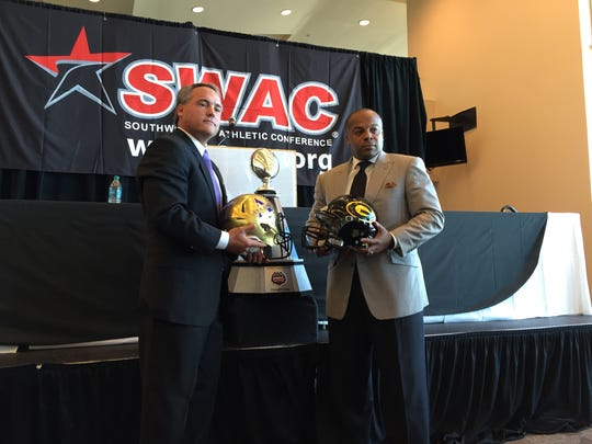 Alcorn State coach Jay Hopson, left, and Grambling coach Broderick Fobbs, right, hold up their respective helmets as a press conference Friday in Houston.