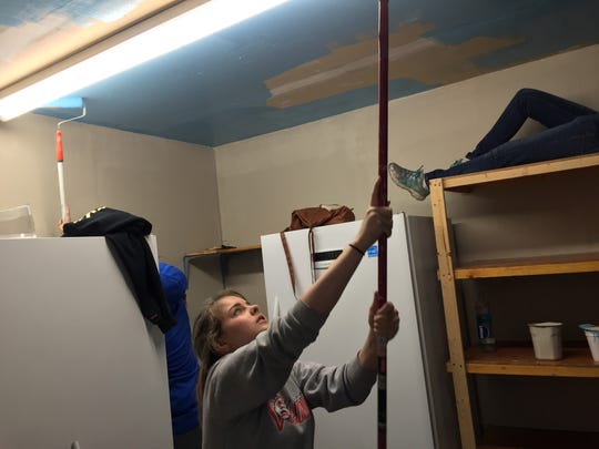 Kacey Whitfield, 13, paints the ceiling of the HOME Youth & Resource Center during a community service project on Saturday, Dec. 3 in Salem, Ore.