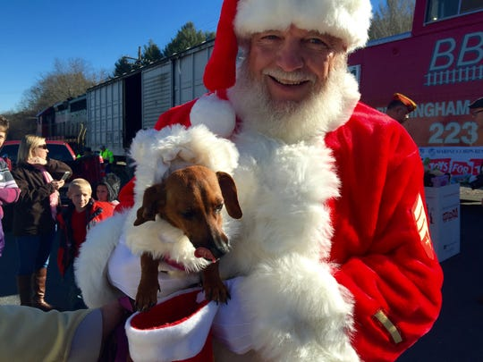 Santa allows Skeeter, a red doxie, to sniff his stocking