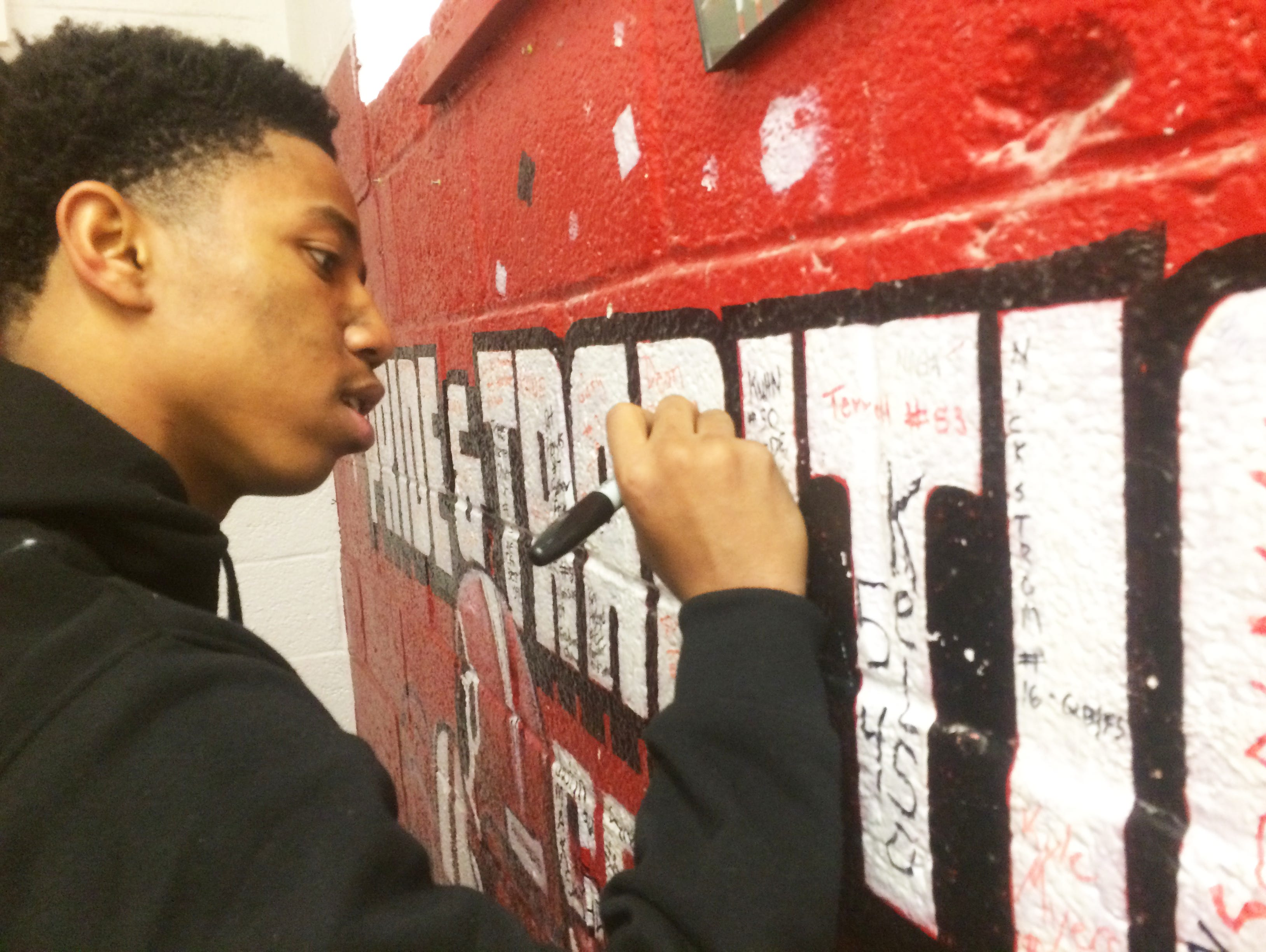 Palmrya High School defensive back/wide receiver Terry Bailey signs his name on the Panthers' locker room wall after the team's Central Jersey Group 1 loss to Shore Regional on Dec. 5.