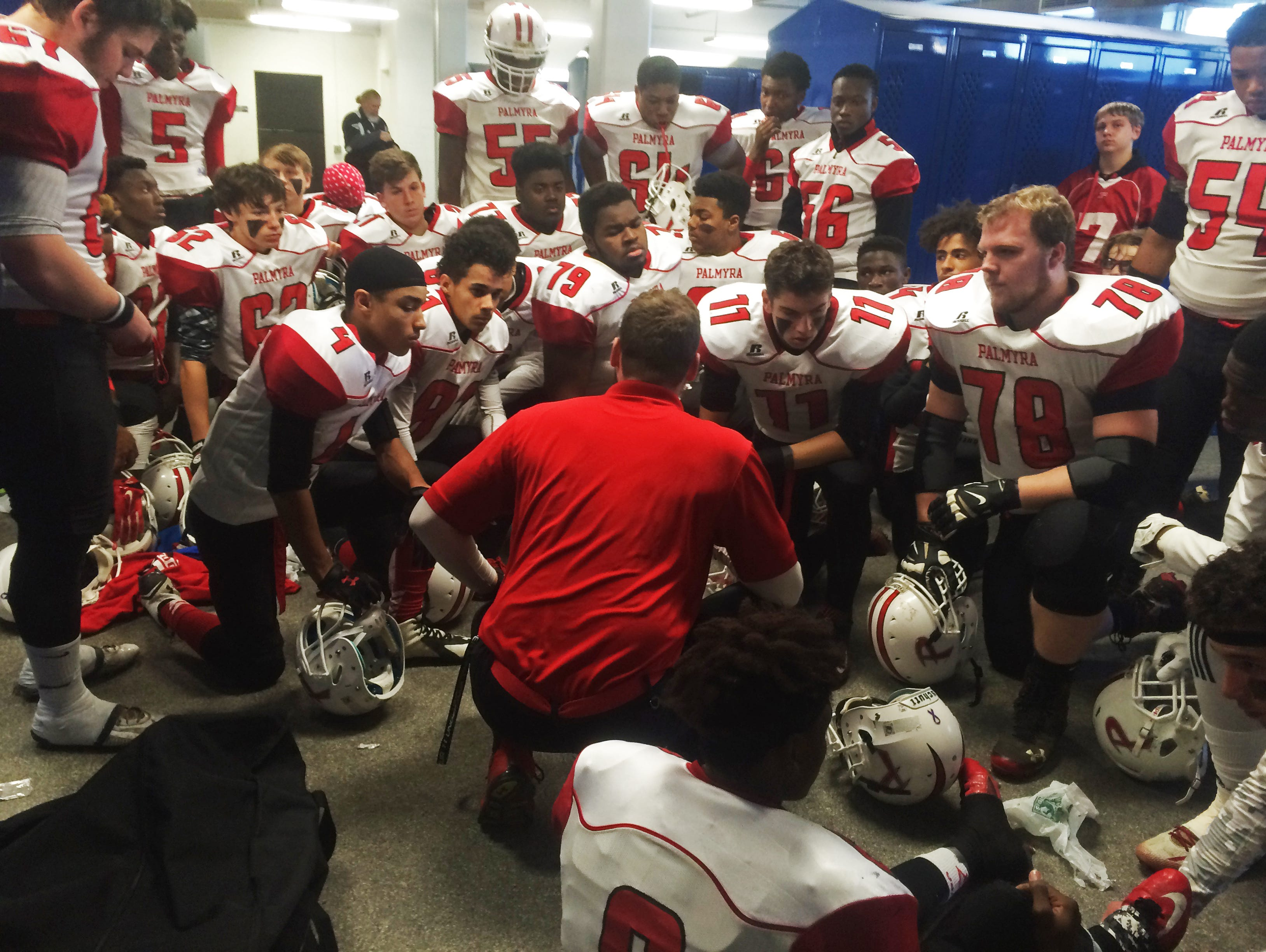 Palmyra High School's football team gathers around assistant coach Conor Geisel, middle, for a speech before Dec. 5's Central Jersey Group 1 final at Kean University.
