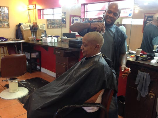 JJ Chaney cuts the hair of Karen Johnson at his Veronica Shoemaker Boulevard shop.