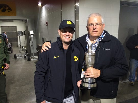 Retired Register columnist Rick Brown spends a moment with Zach Johnson's Claret Jug.