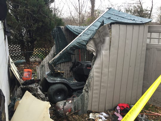 A riding mower sits inside a melted plastic shed behind