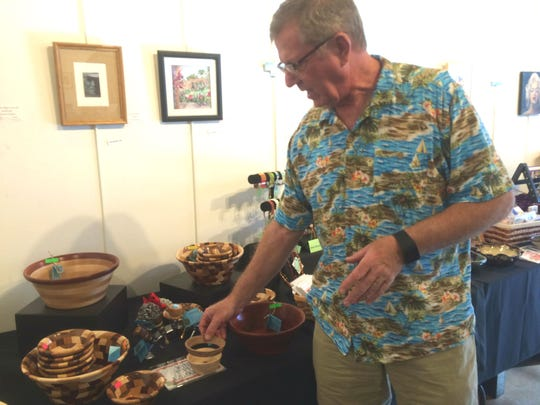 Woodwork artist Dan Kizerian touches his bowls in the Mesquite Fine Arts Gallery.