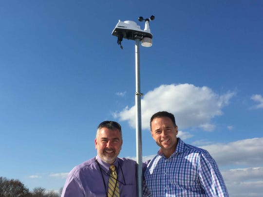 Holland Brook School Principal Paul Nigro (above left) and meteorologist John Marshall stand next to the weather gauges which are mounted on the school's roof.  This wireless station sends a signal to a weather station in the school, and current weather conditions can then be viewed on the school's website (http://www.weatherlink.com/user/hbsweather/).  Principal Nigro also announces the day's weather conditions during morning announcements.  Marshall, whose children attend Readington schools, was instrumental in having the weather station installed at the school.