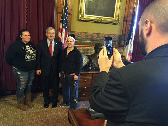 Robyn Kockorsky, left, and Mickayla Meyer, right, pose for a photo with Iowa Gov. Terry Branstad on his record 7,642nd day in office.
