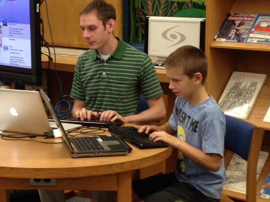 David Schubert, the technology resource coordinator for DeSoto Trail Elementary, works one on one with a student at the media center.