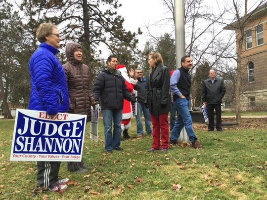A crowd holding signs gathers outside of Old Main on the University of Wisconsin-Stevens Point campus before Portage County Circuit Judge Robert Shannon announced his election bid, Tuesday Dec. 15, 2015.