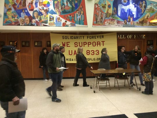 Members of UAW Local 833 arrive at Plymouth High School