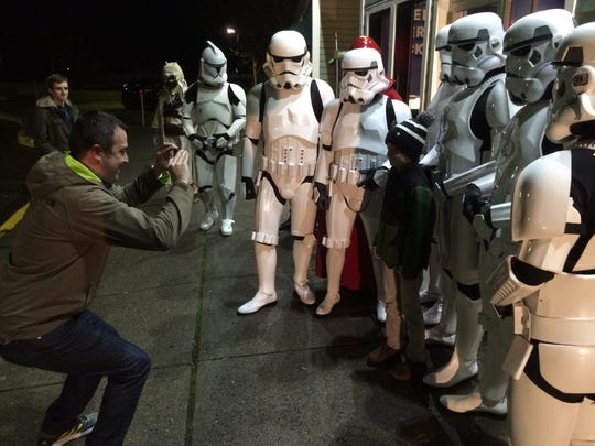 "Bill Leonard, 40, of Essex, takes a photograph of his son, Charlie Leonard, 7, with Stormtroopers gathered at Essex Cinemas for ""Star Wars: The Force Awakens."""