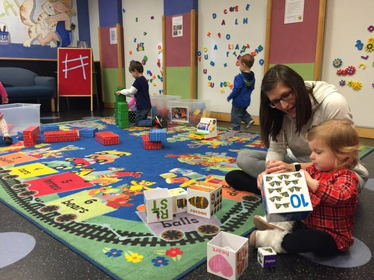 Kristen Pytel of Macomb Township plays with her 18-month-old daughter Macey while her 5-year-old son, Harrison, back left, plays during block party activity time Dec. 17, 2015, at the Clinton-Macomb Public Library's main branch in Clinton Township.