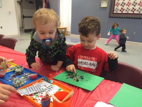 Archer Paulkett, 3, and Grayson Paulkett, 1, make holiday crafts at the Worcester County Library Ocean Pines branch Dec. 17, 2015.