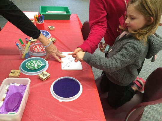 Callie Flakowitz, 4, makes holiday cards using stamps and ink.