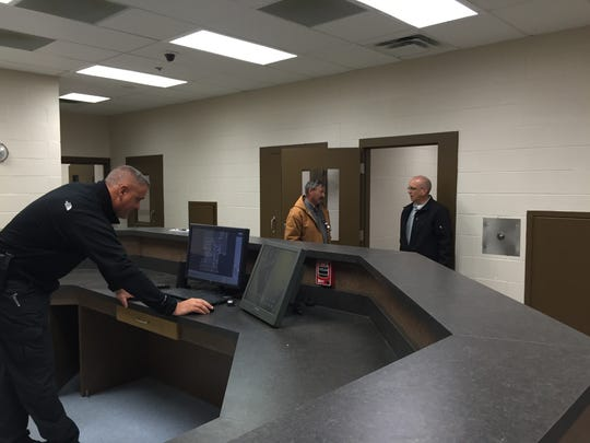 Chief Deputy Scott Templon, left, checks a computer in the booking area of Stewart County's new jail while Sheriff Deryk Wyatt, right, chats with Construction Superintendent Bryan Parkhill.