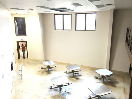 Inmates can eat at metal tables in a common area of