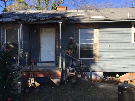 John Taylor stand in front of his East 69th Street home that was badly damaged in a November fire. A smoke detector installed by Shreveport Fire Department is credited with saving his life.