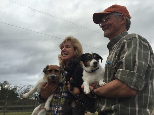Tracy and Bobby Hewlett hold their dogs following a media conference about the recent bombing at their farm. The Hewletts said they feel blessed to be alive and plan to enjoy the Christmas season.