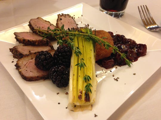 Seared, cracked peppercorn encrusted duck breast with blackcherry port reduction, sweet potato cake and grilled leek, prepared by Chef Ingrid Dellatorre.