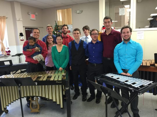 Members of Rutgers Percussion Ensemble -(front row) Joe Tompkins, holding 2-year-old Jayla,  Allegra Pin, Christine Chen, Anthony Eskin, Dan Vaughan, Tom O'Hara and Brant Roberts. (back row) Mike Winnicki, Greg Riss and Joe LaVecchia - performed  a variety of holiday favorites for residents of the Ozanam Family Shelter on Dec. 18.