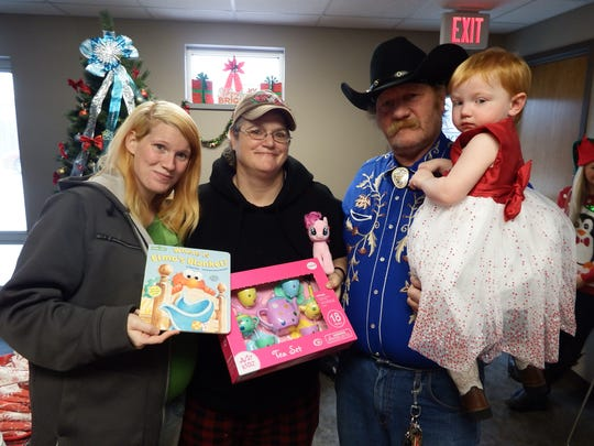 Anna, Heather, Cowboy and Carol Walker pose with toys Santa gave to Carol at the Free Lunch Program's Christmas Day lunch in Iowa City on Friday, Dec, 25, 2015.