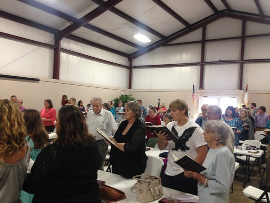 Members of Falcon Baptist Church sing hymns during Sunday's service in the Fellowship building. Falcon Baptist Church was hit by a tornado on Dec. 23, damaging the sancuary and many homes on the road.