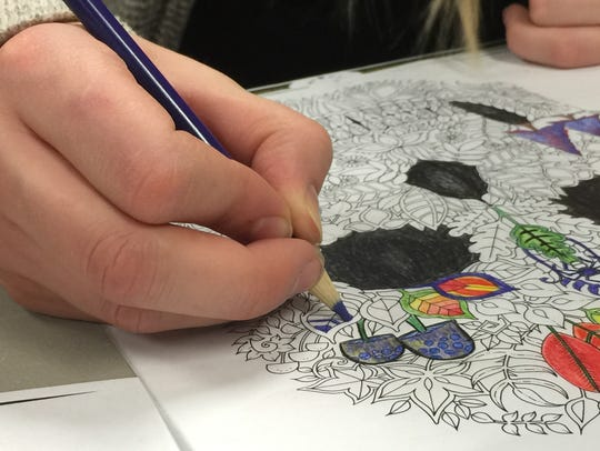 The author colors an illustration from an adult coloring