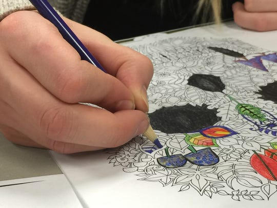 The author colors an illustration from an adult coloring book.