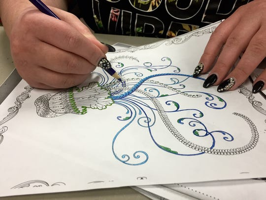 "An attendee at Marathon County Public Library's ""Inside the Lines: Adult Coloring Party"" series Tuesday colors an intricately designed jelly fish."