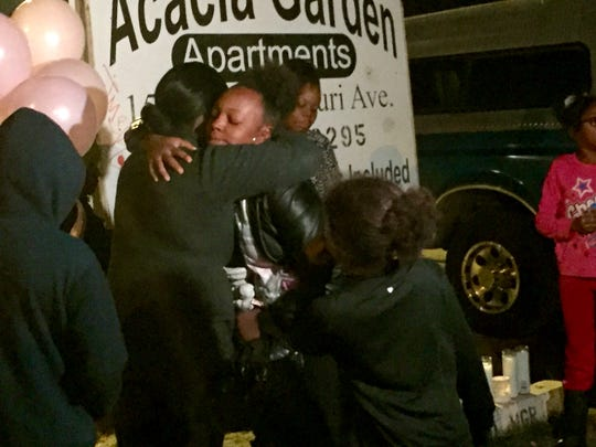 Aeysha Smith hugs friends and family during a vigil