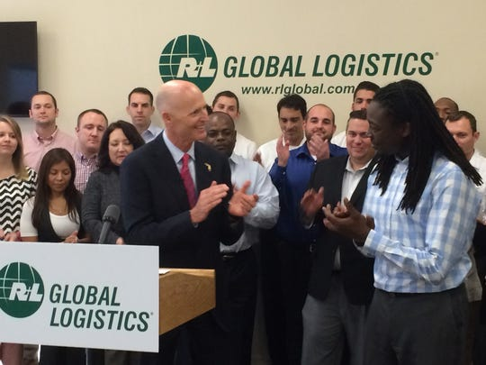 Gov. Rick Scott and R+L Global Logistics employee Munya Chiware applaud each other Monday at a jobs announcement event.