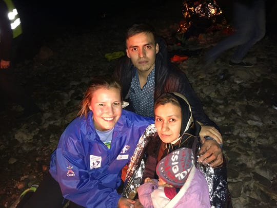 College of St. Benedict student Amy Larson poses with a Syrian refugee family while working with relief agencies in late November on the Greek island of Lesbos.