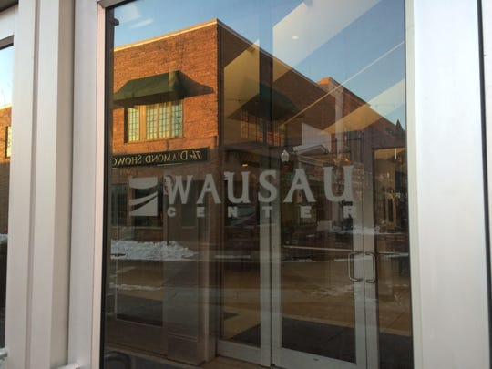 Downtown stores are reflected in the glass door of Wausau Center mall on Jan. 5.