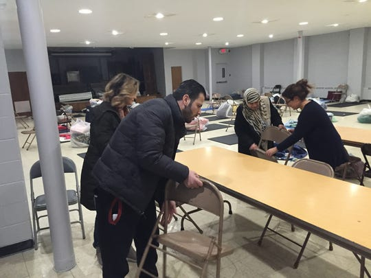 Syrian refugees Anis Hamad (in blue coat) and Entesar Al-Rachdan (with scarf), volunteer on Jan. 5, 2016, to help a temporary homeless shelter at Renaissance Vineyard Church in Ferndale.