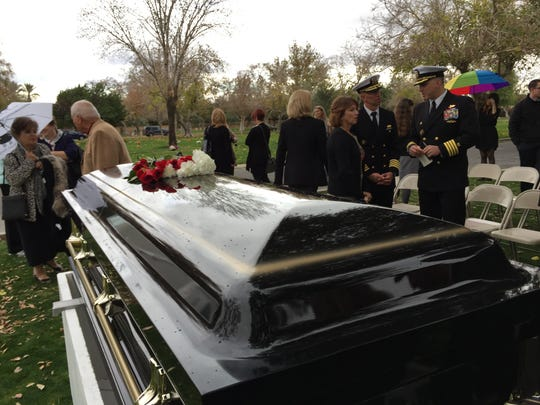 Roses and carnations were placed on top of the casket of U.S. Navy Admiral Ben Montoya just as rain began to fall at the Coachella Valley Cemetery in Coachella on Wednesday, Jan. 6, 2016.
