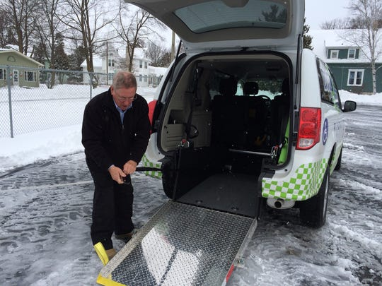 Door 2 Door driver Jim McClellan demonstrates how the wheelchair and scooter lift system works in his van.