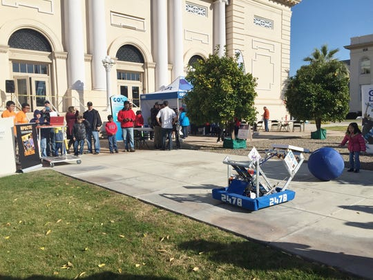 Ari, 6, rolls a ball toward the catching-and-tossing robot created by the Westwood High School robotics team.