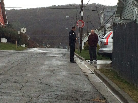 A Johnson City Police Officer (left) speaks with a resident of a home on Hillside Street in Johnson City about the location of an arrested shooter's missing handgun.