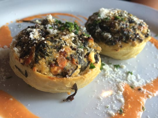 Roasted artichoke bottoms stuffed with goat cheese, spinach, tomatoes and quinoa, then served atop a swoosh of red-pepper coulis from The Other Side Bistro in Bonita Springs.